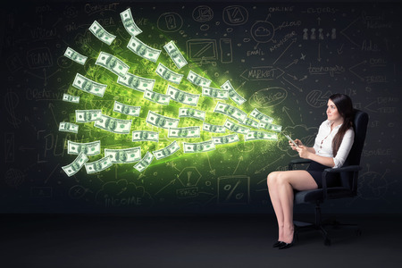 money transfer: Businesswoman sitting in chair holding tablet with dollar bills coming out concept on background