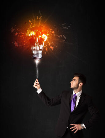 smithereens: Businessman with an explosion bulb on black background