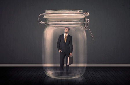Businessman trapped into a glass jar concept on background photo