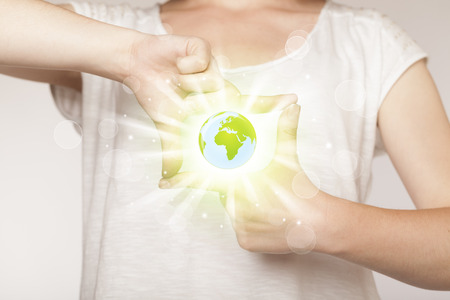 international recycle symbol: Hands creating a form with shining globe in the center Stock Photo
