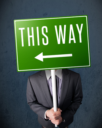 Businessman standing and holding a green direction sign in front of his head photo
