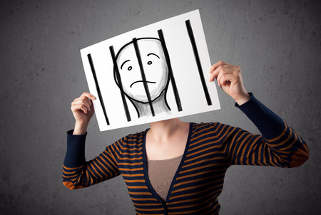 Woman holding a paper with a prisoner in jail behind the bars on it in front of her head photo