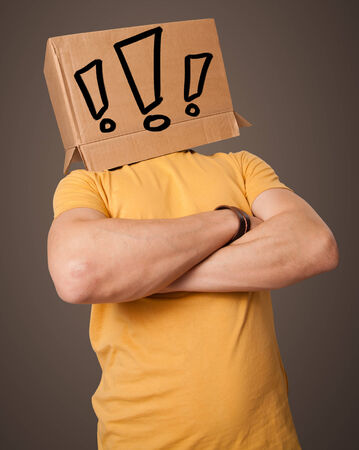 Young man standing and gesturing with a cardboard box on his head with exclamation point photo