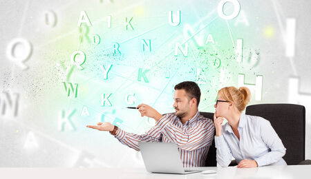 Business people at white desk with green word cloud photo