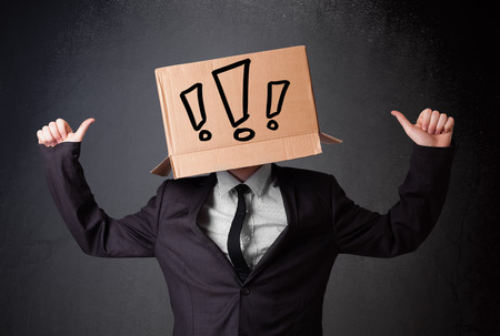 masquerader: Businessman standing and gesturing with a cardboard box on his head with exclamation point Stock Photo