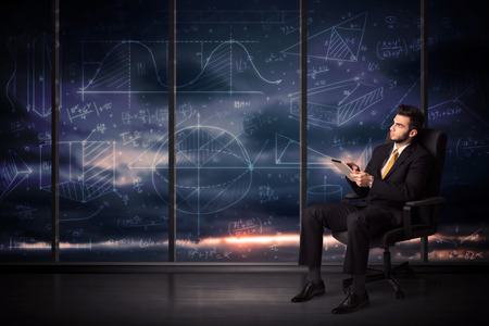 Businessman holding tablet in office room with graph charts on window concept photo