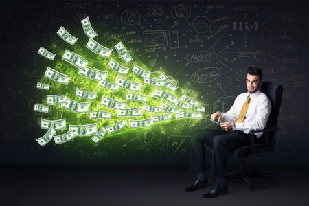 Businessman sitting in chair holding tablet with dollar bills coming out concept on background photo