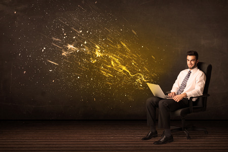 Businessman with laptop and energy explosion on background concept photo