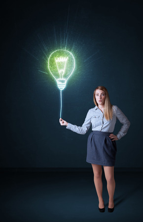 Businesswoman hold a shining idea bulb on a blue background photo