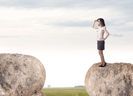 barrier free: Young businesswoman standing on edge of rock mountain