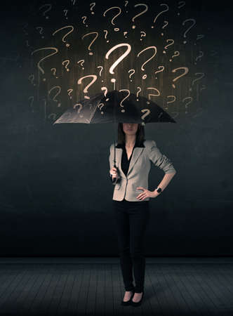 Businesswoman with umbrella and a lot of drawn question marks concept on background photo