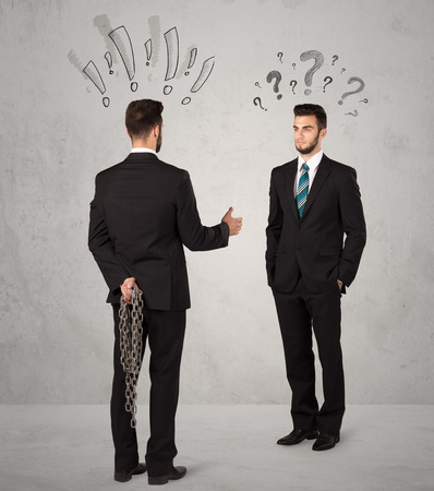 Ruthless businessman handshake with drawn exclamation and question marks around them head photo