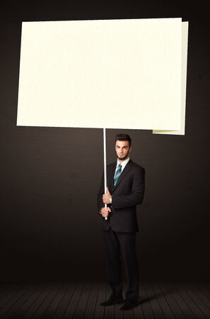 Young businessman holding a big, white post-it paper photo