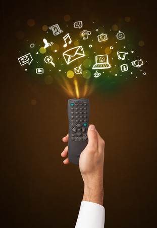 Hand holding a remote control, social media icons coming out of it photo