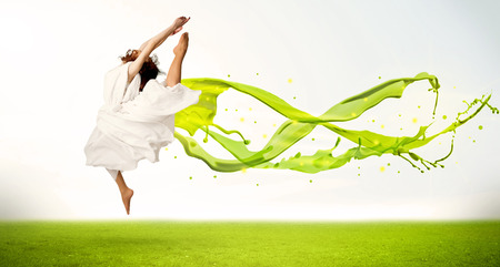 Pretty girl jumping with green abstract liquid dress concept in nature photo