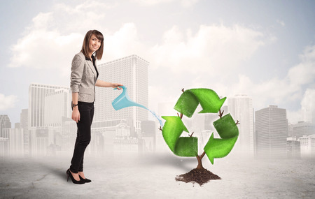 Business woman watering green recycle sign tree on city background concept photo