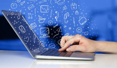 mercadeo en red: Ordenador port�til con iconos y s�mbolos dibujados a mano comming fuera Foto de archivo