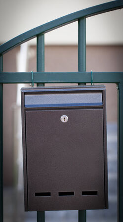 metal mailbox: Cloes up of a mailbox on the street with fence Stock Photo