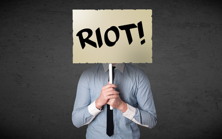 riots: Businessman holding a demonstration board with riot sign in front of his head