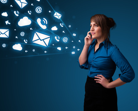 Young lady standing and making phone call with message icons photo