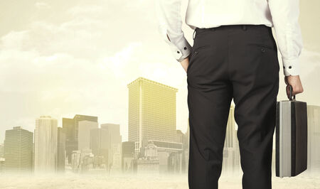creative force: Businessman from the back in front of a city view with sunshine