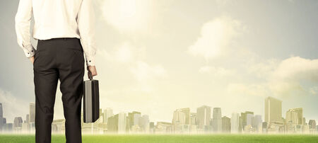 creative force: Businessman from the back in front of a city view with clouds and grass Stock Photo