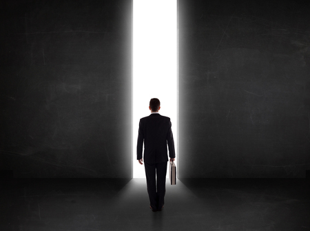 Business person looking at wall with light tunnel opening concept photo