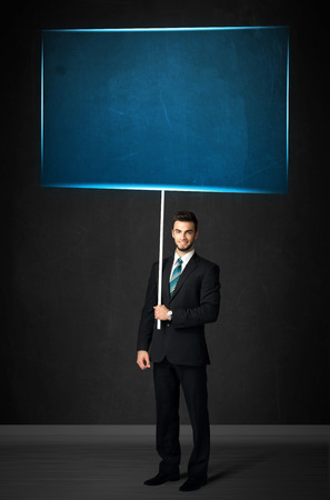 Young businessman holding a big, blue board photo