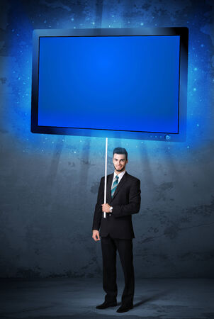 Young businessman holding a big, blue shining tablet photo