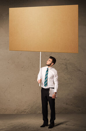 Young businessman holding a blank brown cardboard photo