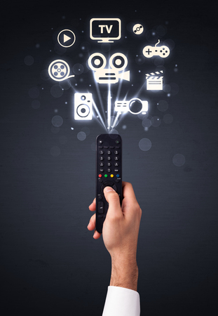 Hand holding a remote control, media icons coming out of it photo
