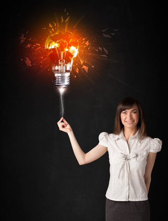 smithereens: Businesswoman with an explosion bulb on black background