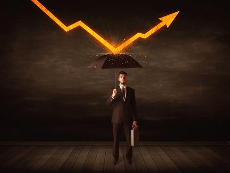 Businessman standing with umbrella keeping orange arrow concept on background photo