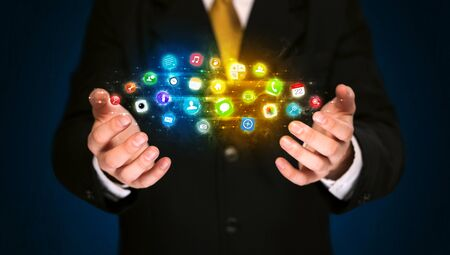 Businessman holding a shining app icon cloud in front of his body photo