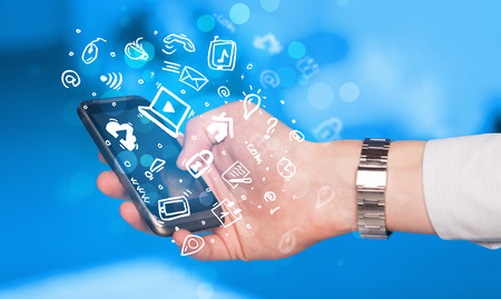 Hand holding smartphone with media icons and symbol collection Stock Photo
