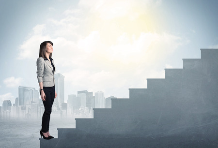 Businesswoman climbing up a concrete staircase concept on city background photo