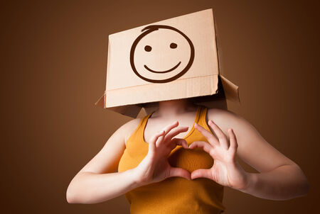 masquerader: Young girl standing and gesturing with a cardboard box on her head with smiley face Stock Photo