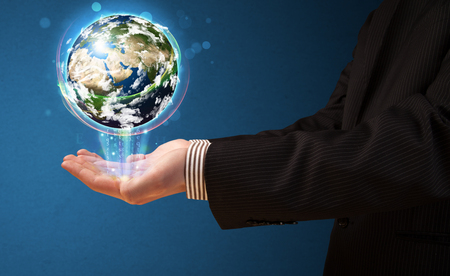 Young businessman holding in his hand a glowing earth globe, Elements of this image furnished by NASA photo