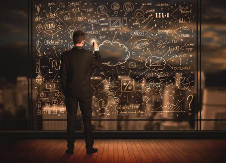 Zakenman tekening business plan op glasvenster met bokeh achtergrond Stockfoto