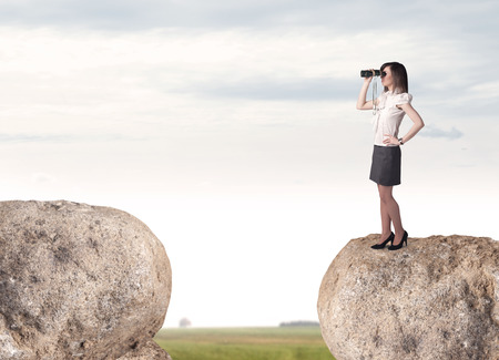 bridging the gap: Young businesswoman standing on edge of rock mountain
