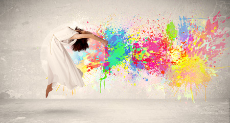 ink splatter: Happy teenager jumping with colorful ink splatter on urban concept