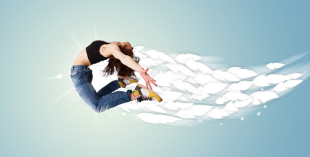 Healthy young woman jumping with feathers around her concept on bright  Stok Fotoğraf