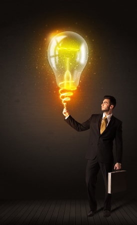 Businessman holding a shining idea bulb photo