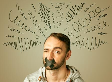 guardar silencio: Hombre joven con la boca pegada y l�neas rizado alrededor de su cabeza Foto de archivo