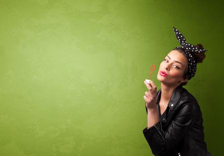 lips kiss: Beautiful woman blowing soap bubble on copyspace green