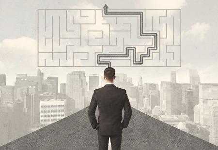 Zakenman kijken naar de weg met een doolhof en oplossingsconcept