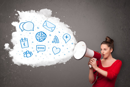 shouting: Young woman shouting into loudspeaker and modern blue icons and symbols come out Stock Photo
