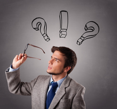 question mark background: Young man standing and thinking with question marks overhead