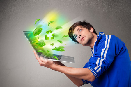 Casual young boy holding laptop with recycle and environmental symbols photo