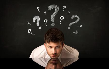 Uomo d'affari depresso seduto sotto un punto interrogativo
